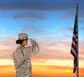 Closeup of an American Female Soldier in combat uniform saluting a flag at sunset.