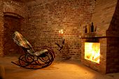 image of cozy hearth  - Rocking chair by the fireplace in brick room with candles - JPG