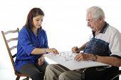 Un atractivo joven voluntario jugando dominó con un anciano en silla de ruedas.  En una parte posterior del blanco