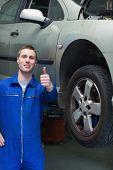 Portrait of  car mechanic gesturing thumbs up in workshop