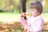stock photo of leaf-blower  - beautiful little girl making bubble blower on the autumn forest - JPG