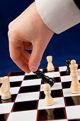 Hand holding black chessman against blue background