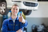 Portrait of male mechanic giving thumbs up in workshop