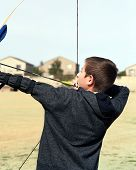 stock photo of fletching  - Young boy archer drawing back a bow and arrow - JPG