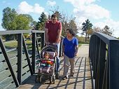 Young family walking on bridge.