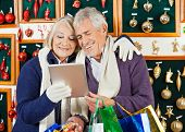 Happy senior couple with shopping bags using digital tablet at Christmas store