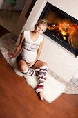 Beautiful young pregnant woman at home near the fireplace