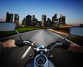 picture of pov  - Driver riding motorcycle on an asphalt road at night towards big city - JPG