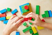 Two hands building a tower with colorful wooden building blocks