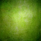 Abstract green background or paper with bright center spotlight and dark border frame with grunge ba