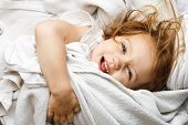 Happy young child rolling in white covers