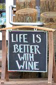 stock photo of woodgrain  - Life is Better with Wine sign at a oceanside vendor - JPG