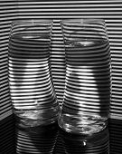 stock photo of refraction  - Two curved glasses refracting a striped background and their reflections cause the light to form the letters N and A - JPG