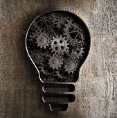 lighting bulb business concept with working gears and cogs in rusty metal background