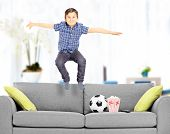 Overjoyed boy jumping on couch at home shot with tilt and shift lens
