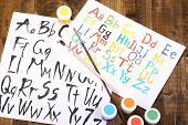Alphabet watercolors on wooden background
