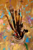 Brushes  in vase on wooden background