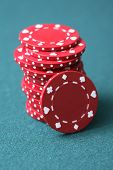 Red gambling chips on green background