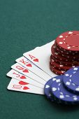 Playing cards and gambling chips on green background