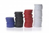 Stacks of various colored gambling chips on white background