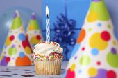 Birthday cupcake with lit candle on blue background