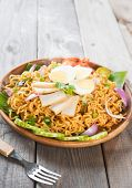 Spicy dried curry instant noodles or Malaysian style maggi goreng mamak.  Asian cuisine, ready to serve on wooden dining table setting. Fresh hot with steamed smoke.