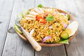 Spicy fried curry instant noodles or Malaysian style maggi goreng mamak.  Asian cuisine, ready to se