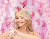 health, beauty and spa concept - beautiful woman applying cream