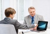business, advertisement, technology and office concept - older man and young man with laptop compute