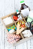 Medical pills,stethoscope,  ampules in wooden box, on color wooden background