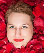 rose petals around a beautiful woman's face.