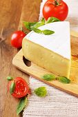 Tasty Camembert cheese with tomatoes and basil, on wooden table