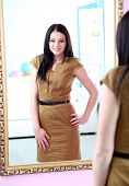 Young beautiful woman standing front of mirror in room