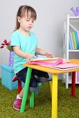Little girl reads book sitting at table in room