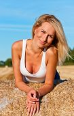 Beautiful woman in  short  posing on a wheat bale