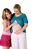 stock photo of niece  - Pregnant aunt showing het belly to her young niece - JPG