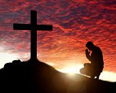 Silhouette of man praying to a cross with heavenly cloudscape sunset concept for religion, worship,