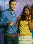 Beautiful young couple with drinks at night club