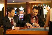 stock photo of roulette table  - Two young men in suits behind gambling table in a casino - JPG
