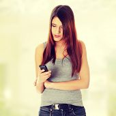 Teen girl using cell phone sending sms