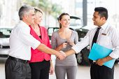 happy middle aged man handshake with car salesman after purchasing a car