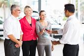 image of showrooms  - friendly salesman handing car key to customer in showroom - JPG