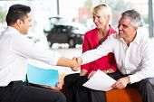 happy car salesman handshaking with senior buyer