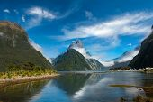 Famous Mitre Peak rising from the Milford Sound fiord and reflecting in water. Fiordland national pa