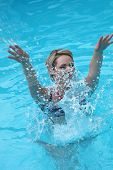Young Woman Splashing In A Swimming Pool