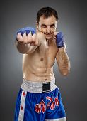 foto of muay thai  - Caucasian kickboxer or muay thai fighter executing a punch on gray background - JPG