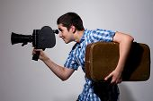 Young Filmmaker With Old Movie Camera And A Suitcase In His Hand