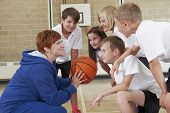 stock photo of motivation talk  - Coach Giving Team Talk To Elementary School Basketball Team - JPG