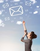 Casual young girl looking at mail symbol clouds on blue sky