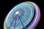 Beautiful Long exposure picture of a ferris wheel rotating vivid colors.